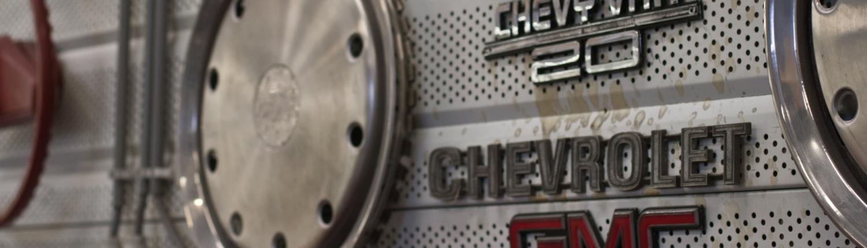 logo-emblemen aan de muur van de werkplaats van PK Cars